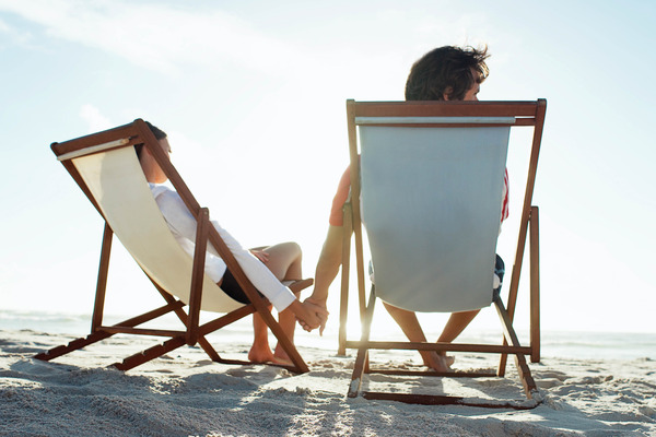 Couple sitting on sand in beach chairs
